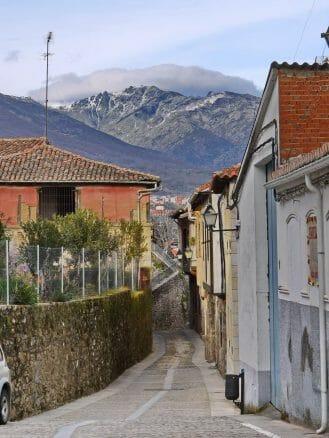 Gasse in Cuacos vor den Bergen der Sierra de Gredos